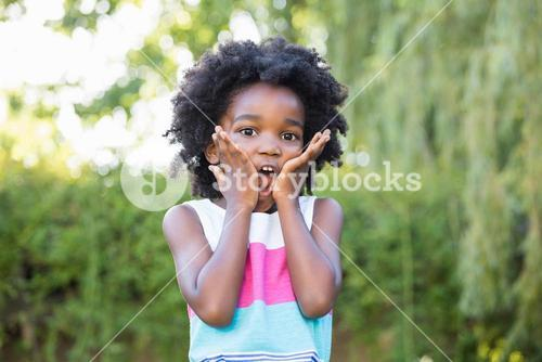 A kid surprised and holding her head in hands