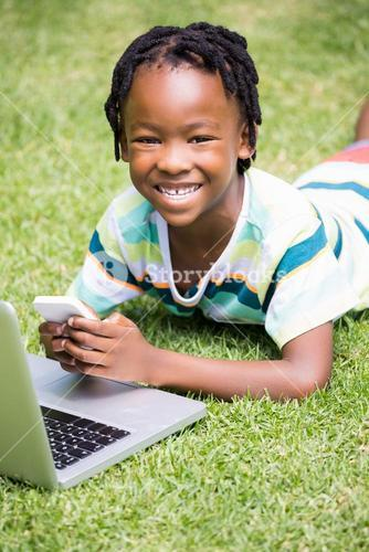 Portrait of kid smiling with a mobile phone and laptop