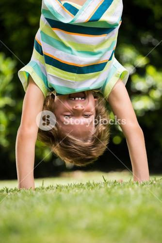 A little boy is playing upside down