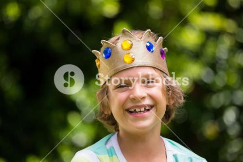 A little boy is holding a crown