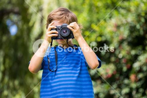 Portrait of young boy taking a photo face to the camera