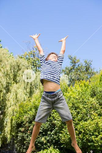 Cute boy jumping with raised arms