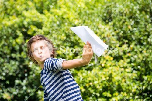 Portrait of cute boy playing with a paper plane