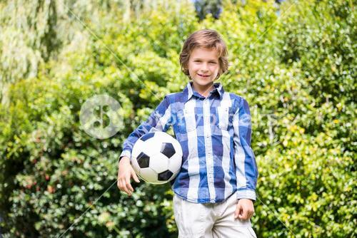 Portrait of cute boy smiling and holding a soccer ball