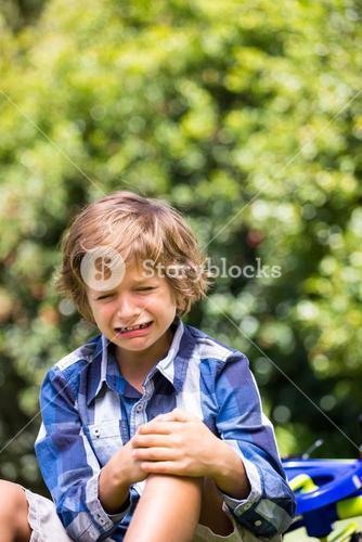 Portrait of cute boy crying cause of his bike fall