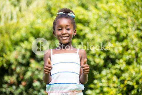 Mixed-race girl smiling and throwing up thumbs