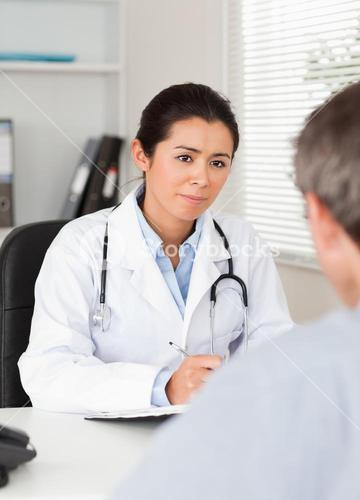 Pretty female doctor listening carefully to a patient