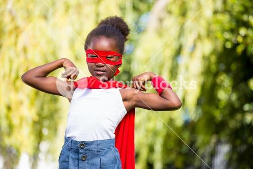 Cute mixed-race girl wearing a fancy dress and showing her biceps