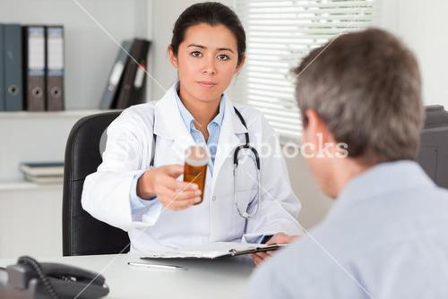 Beautiful female doctor showing a box of pills to the camera