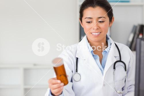 Beautiful smiling doctor holding and looking at a box of pills