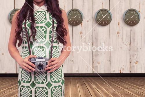Composite image of mid section of woman holding camera