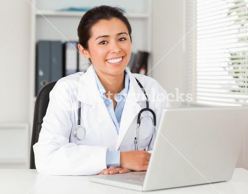Good looking female doctor working with her laptop while posing