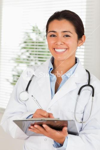 Attractive female doctor with a stethoscope writing on a notebook while standing