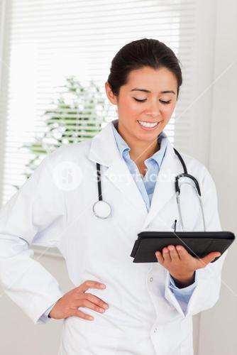Attractive female doctor with a stethoscope holding a notebook while standing