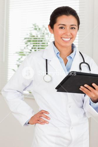 Good looking female doctor with a stethoscope holding a notebook while standing
