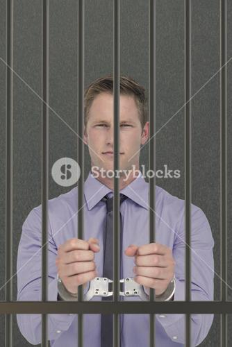 Composite image of handsome businessman wearing handcuffs
