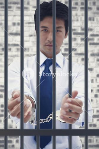 Composite image of portrait of a businessman with handcuffs