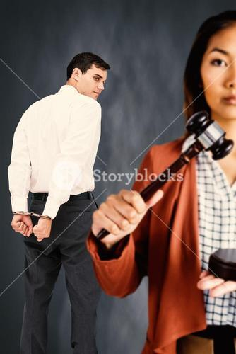 Composite image of businesswoman banging a law hammer on the gavel