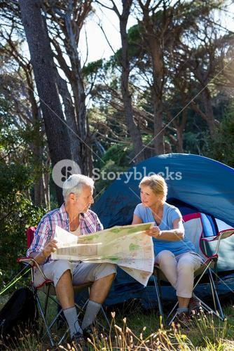 Mature couple looking map on camp site