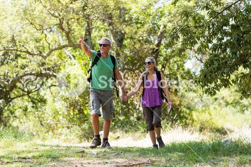 Couple pointing and holding hands each other during a hike