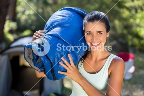 Woman smiling and holding a sleeping bag
