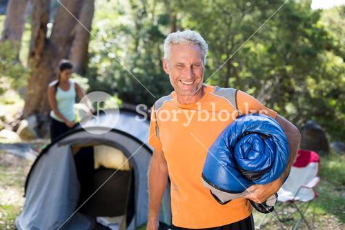 Man smiling and holding a sleeping bag