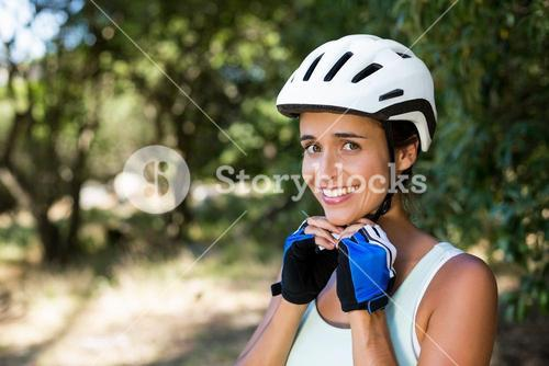 Woman smiling and fastening her cycling helmet