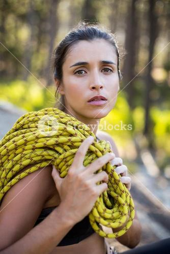 Woman unsmiling and sitting with climbing equipment