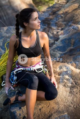 Woman sitting with climbing equipment