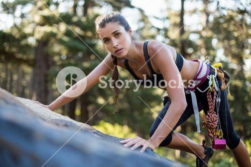 Woman rock climbing and looking the camera
