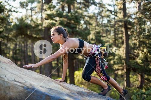 Sporty woman climbing a rock