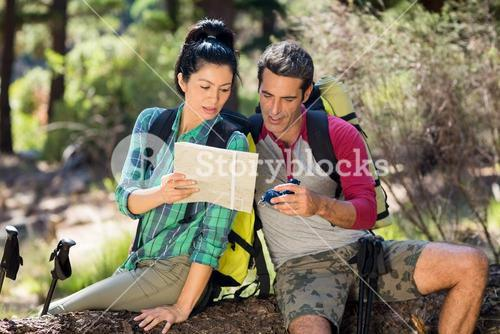 couple hiker studying map and compass