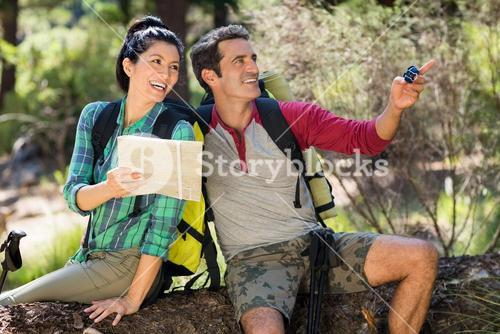 couple smiling and holding map and compass