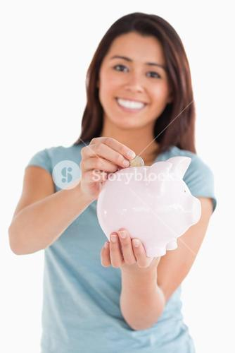 Lovely woman inserting a coin in a piggy bank