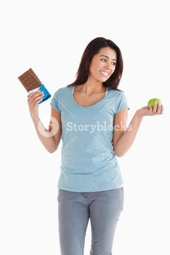 Good looking female holding a chocolate bar and an apple