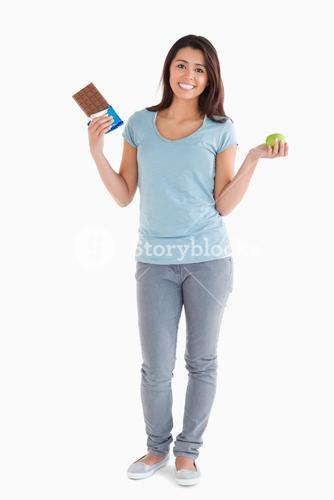 Pretty female holding a chocolate bar and an apple