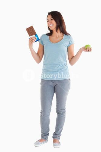 Gorgeous female holding a chocolate bar and an apple