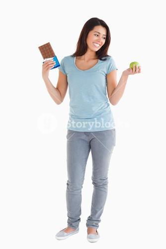Good looking woman holding a chocolate bar and an apple
