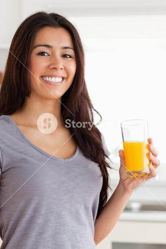 Beautiful woman holding a glass of orange juice while standing