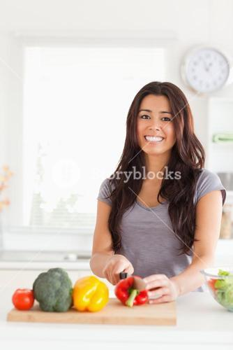 Pretty woman cooking vegetables while standing