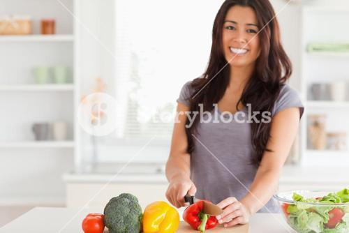 Gorgeous woman cooking vegetables while standing