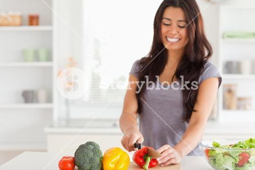 Attractive female cooking vegetables while standing