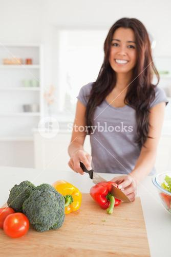 Pretty female cooking vegetables while standing