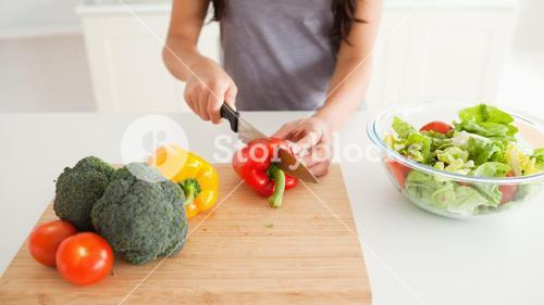 Young female cooking vegetables while standing