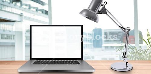 Composite image of desk with laptop