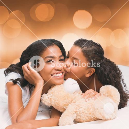 Composite image of pretty woman lying on bed with her daughter kissing cheek