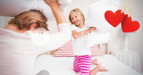 Composite image of mother and daughter fighting with pillows