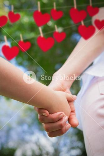 Composite image of mother and daughter holding hands each other