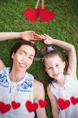 Composite image of mother and daughter lying on grass