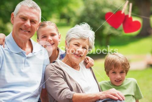 Composite image of smiling senior couple and grandchildren at park